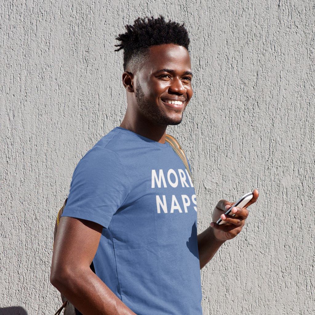 Smiling young man holding a cell phone in his hand wearing a More Naps shirt