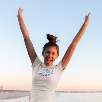 Joyful young woman with messy bun jumps with arms in the air with the beach as a background