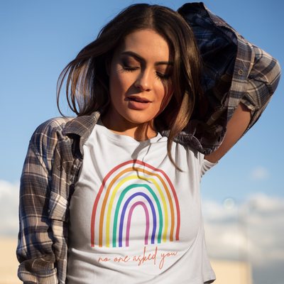 Pretty woman stands outside and wears a flannel shirt over a tshirt with a rainbow that says No One Asked You on it from brazenginger.com.