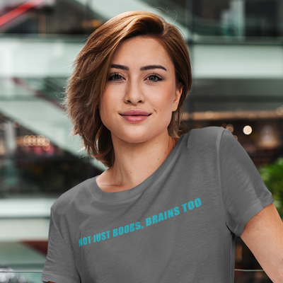 Woman leaning on railing with glass office building in background wearing a Not Just Boobs, Brains Too shirt