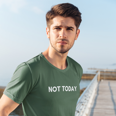 Serious man with stubble looking off in the distance while standing on a pier