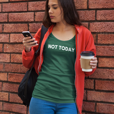 Young brunette woman leaning against red brick wall looking at phone and holding coffee wearing a Not Today shirt