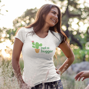 Smiling woman with long brown hair facing another woman while wearing a Not a Hugger cactus shirt