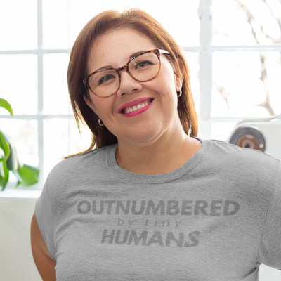 Woman leaning on stove  in sunny room smiling wearing glasses and Outnumbered by Tiny Humans shirt