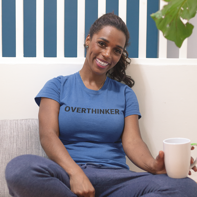 Smiling woman sitting on the floor holding a coffee cup wearing an Overthinker shirt
