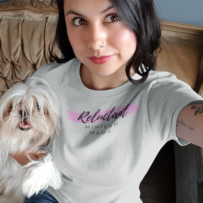 Dark haired woman taking a selfie while holding a little white dog and wearing a Reluctant Minivan Mama shirt