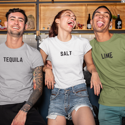 Three friends at a bar being silly wear shirts that say Tequila, Salt and Lime.