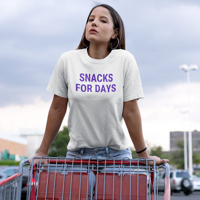 Woman in a parking lot standing on the edge of a shopping cart wearing a shirt that says Snacks For Days