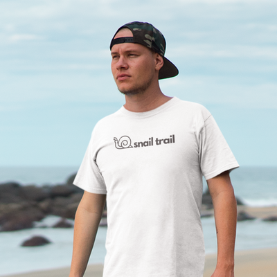 Handsome man with backwards hat and Snail Trail shirt with ocean and rocks in the background