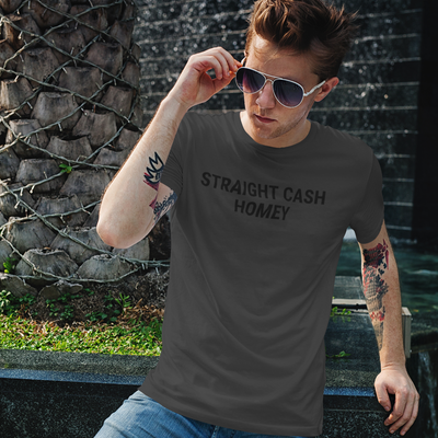 Handsome young man with tattoo sleeves holding aviator sunglasses at his face wearing a Straight Cash Homey shirt