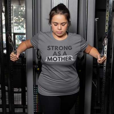 Woman working out on a gym machine wearing a Strong As A Mother shirt