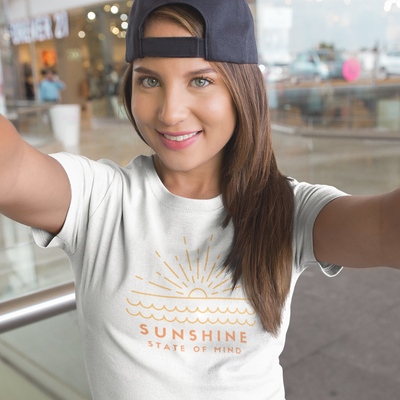 Pretty young woman wearing a backwards navy blue baseball cap takes a selfie while wearing a white shirt that says Sunshine State of Mind
