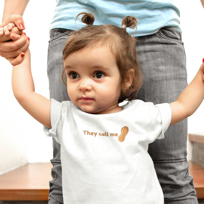 Little girl with two mini bun ponytails wears a shirt that says They Call Me Peanut.