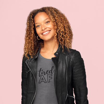 Curly haired woman smiling while wearing a leather jacket and Tired AF shirt