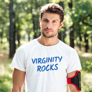 Handsome man with close-cut beard looking at camera standing in the woods wearing a Virginity Rocks shirt