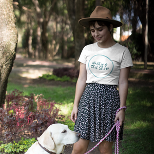 Woman wearing a hat and skirt holding a leash with a sitting yellow lab while wearing a Walking Shit Show shirt