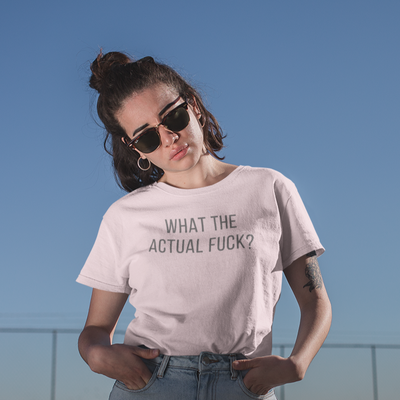 Woman with dark hair and sunglasses looks at the camera with a frown and a What The Actual Fuck? shirt on