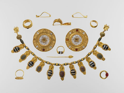 The tomb group represents one of the richest and most impressive sets of Etruscan jewelry ever found. It comprises a splendid gold and glass pendant necklace, a pair of gold and rock-crystal...