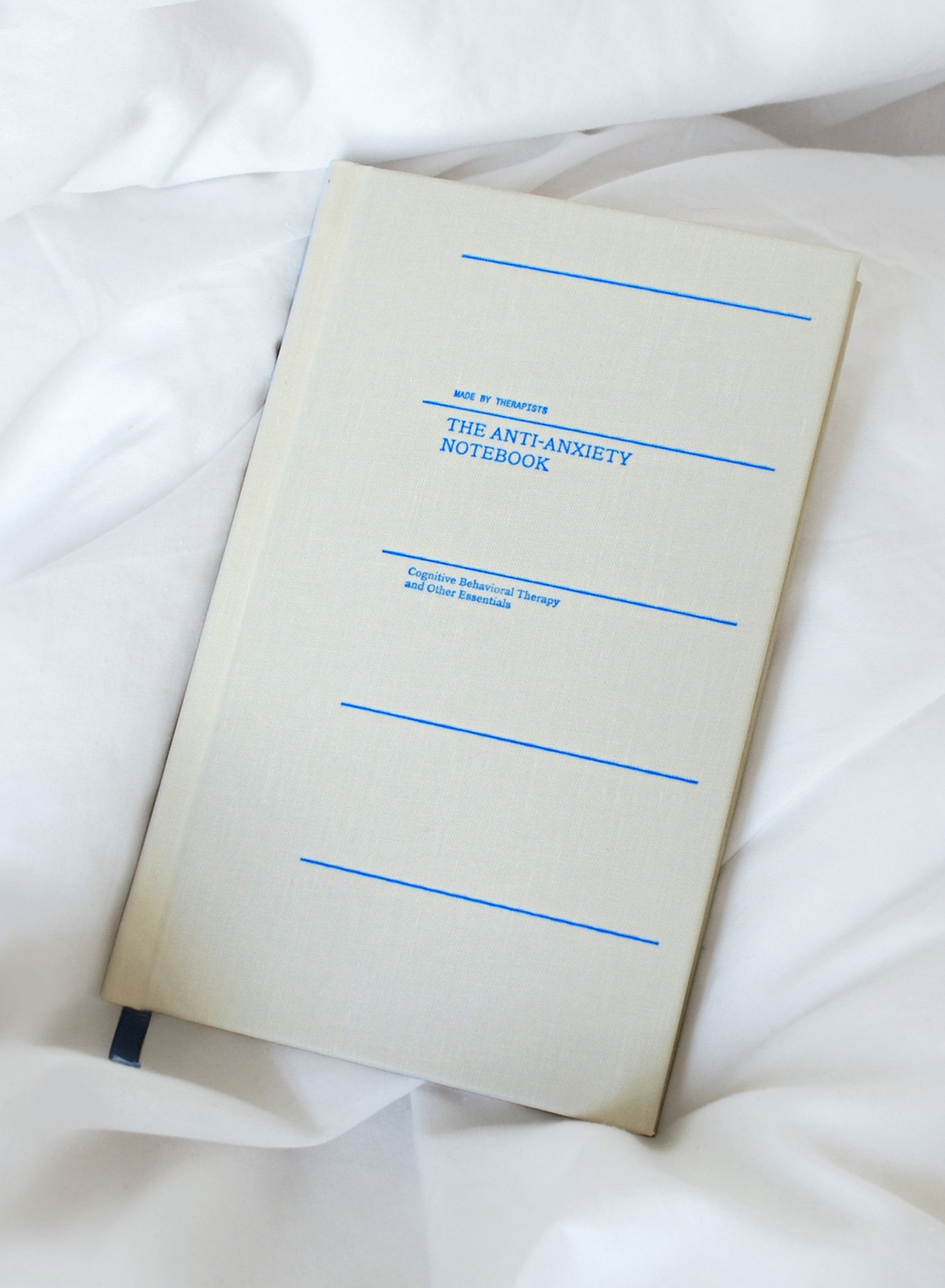 Therapy Notebook laying on bedsheets