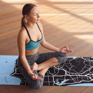 Woman meditating on personalized San Fran print yoga mat