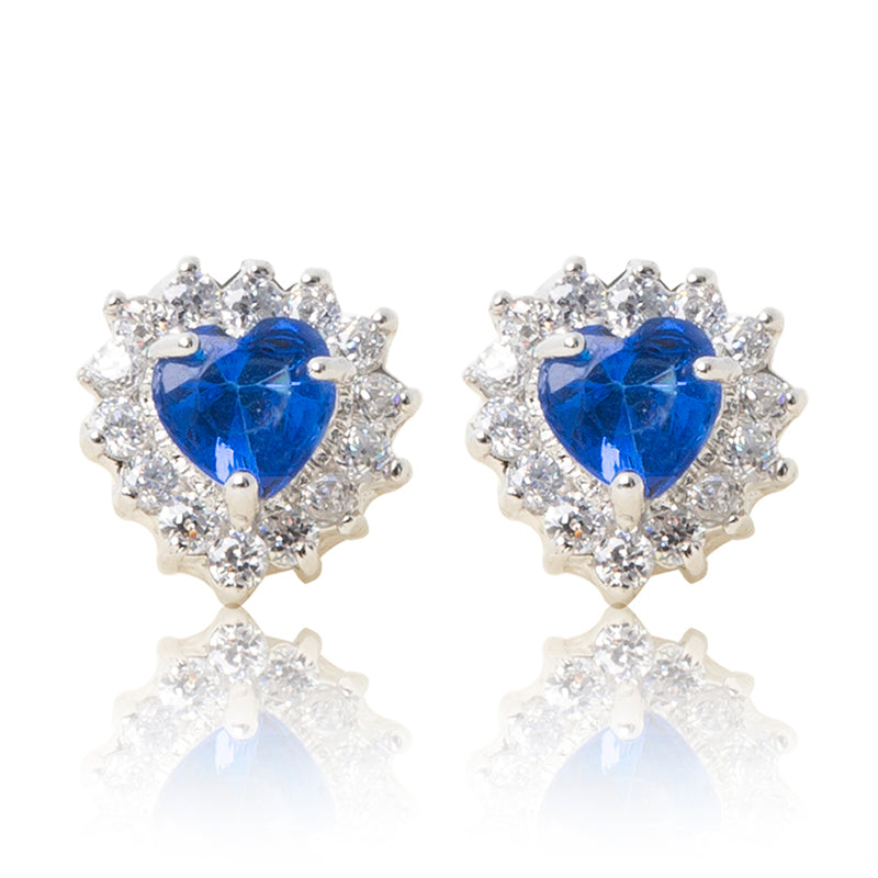 A beautiful tribute to the heart. Delicate rhodium plated studs with clear cubic zirconia stones framing a subtle blue heart stone at the centre. For pierced ears.