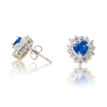 Load image into Gallery viewer, A beautiful tribute to the heart. Delicate rhodium plated studs with cubic zirconia stones framing a subtle blue heart stone at the centre. For pierced ears. Side view (Butterfly and pole closure)