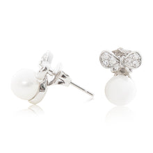 Load image into Gallery viewer, An elegant pair of stud faux pearl earrings finished with rhodium plating and cubic zirconia encrusted bows side view (butterfly and pole closure)