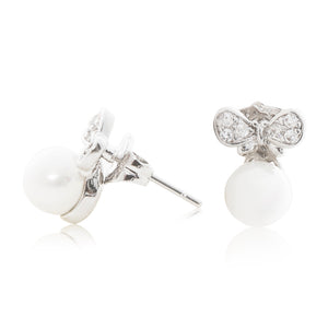 An elegant pair of stud faux pearl earrings finished with rhodium plating and cubic zirconia encrusted bows side view (butterfly and pole closure)