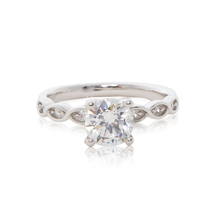 A delicate 925 sterling silver ring with a round brilliant cubic zirconia centre stone with ornate entwined cubic zirconia stone embedded shoulders.