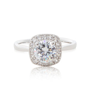 A striking round brilliant cubic zirconia stone surrounded by bead-set cubic zirconia stones evoking a cushion cut guise set in a 925 sterling silver ring.