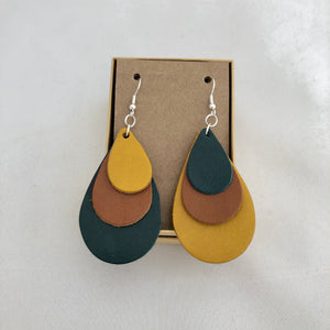 Tri Color Rainbow Earrings in Teal Brown and Yellow. This pair of earrings features a mix-matched order of color, so one earring is yellow, brown, and teal, whereas the other is teal, brown, and yellow. The earrings are pictured on a brown card in a brown jewelry box, which both come included with the earrings. They are pictured against a white background.