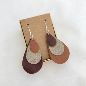 Tri Color Rainbow Earrings in Shades of Brown. This pair of earrings features a mix-matched order of color, so one earring is light brown, spotted tan, and dark brown, whereas the other is dark brown, spotted brown, and light brown. The earrings are pictured on a brown card in a brown jewelry box, which both come included with the earrings. They are pictured against a white background.