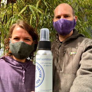 Miranda wearing the olive/light blue face mask and Todd wearing the purple/mauve face mask and holding the all-natural hand sanitizer