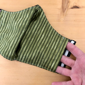 Close up of one side opening of filter pocket on rainbow face mask. There are openings for the filter pocket on both sides of the mask.