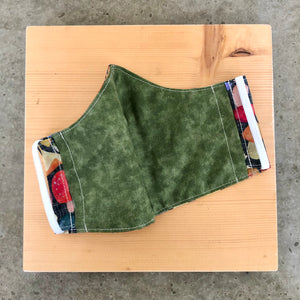 Inside view of the mushroom mask, showing the olive green fabric and ear elastic.