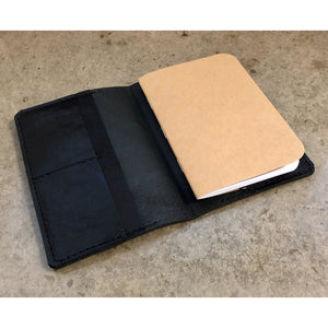 All Black Leather Passport Wallet, pictured holding a small complimentary notebook made with recycled paper