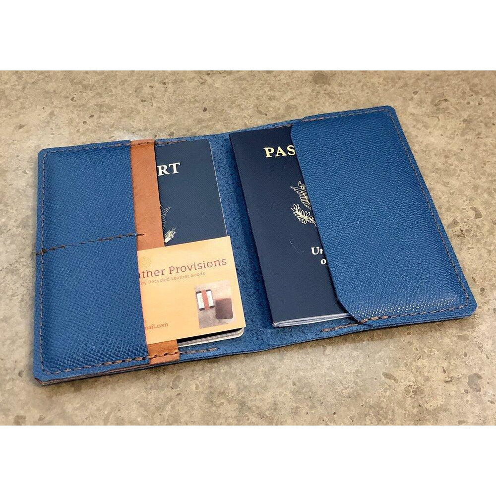Leather Passport Wallet in turquoise with brown pocket accent. Pictured holding 2 passports and a business card.
