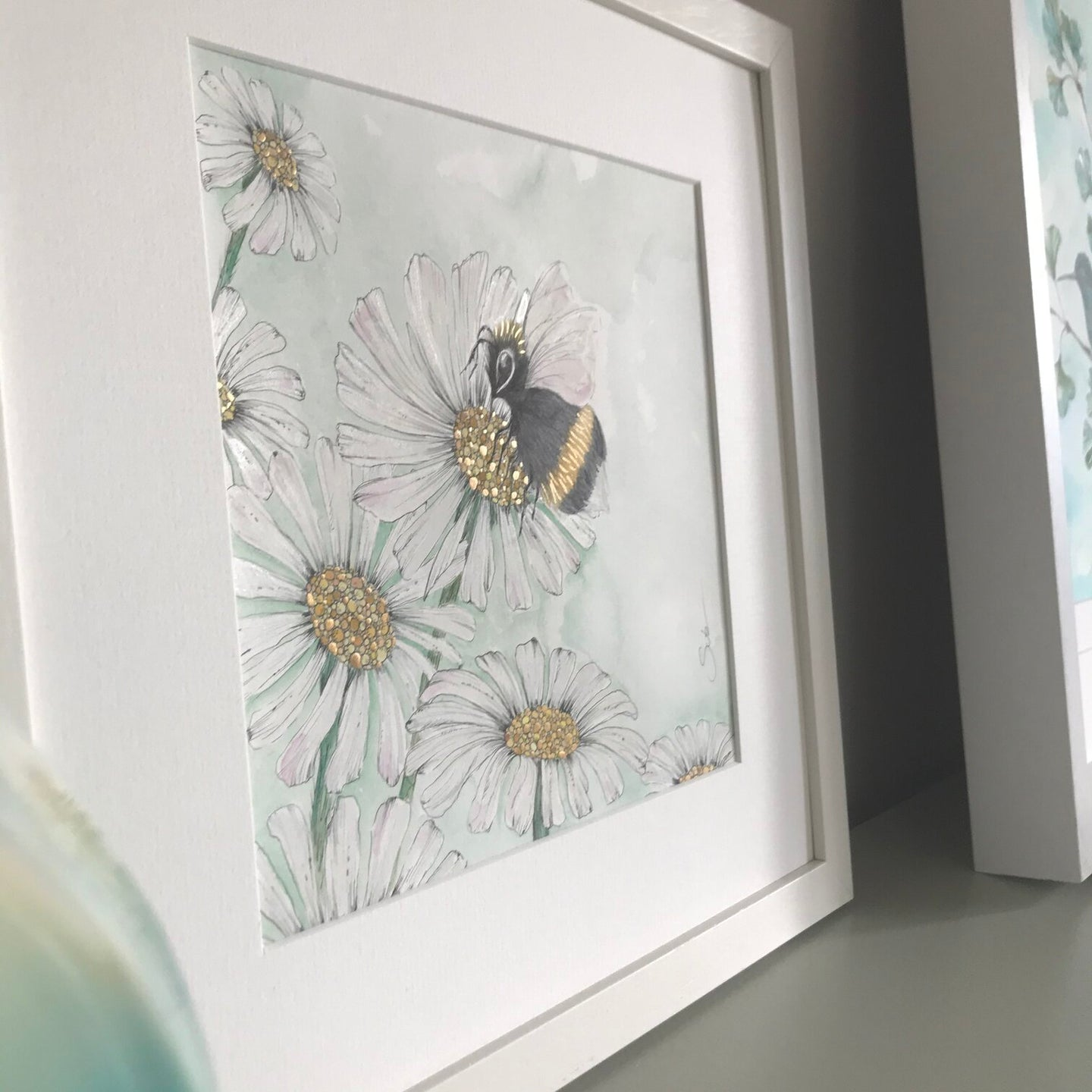 Watercolor Painting of a Bumblebee hovering over a bunch of Daisies with Gold Pollen