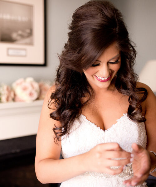 Brunette Bride Putting On Bracelet With Hair and Makeup Done