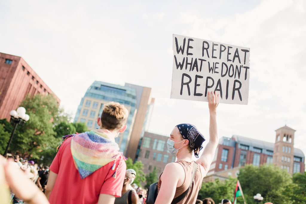 "Woman holding a sign ""we repeat what we don't repair"" Pride KosmicKult"