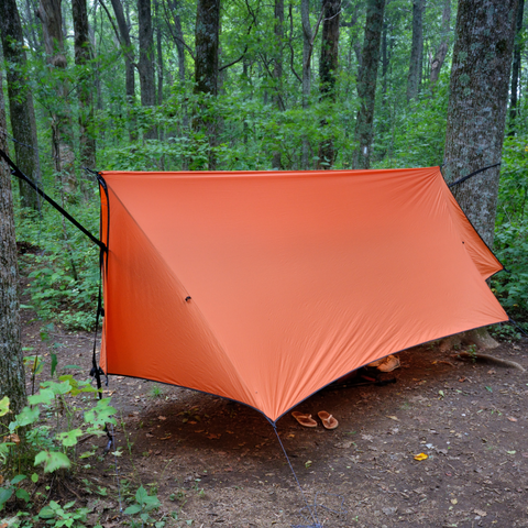 Putting up a fly shelter in your campsite will keep you and your gear dry.