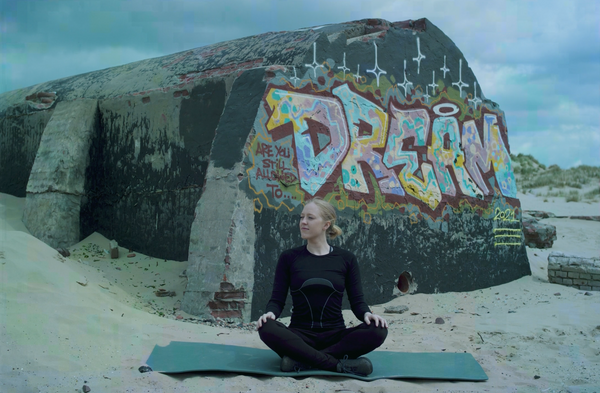Woman sat peacefully with Dream written in graffiti in the background
