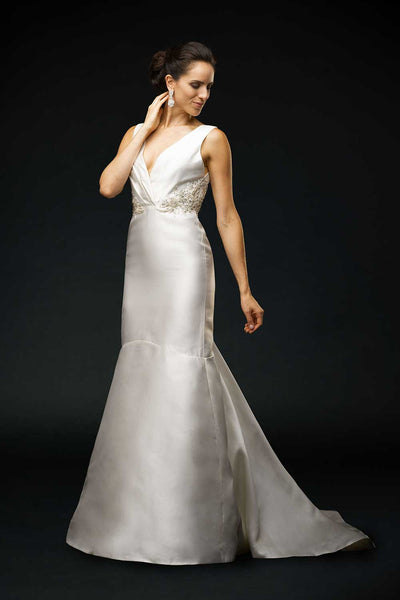 Bride wearing wedding gown with Silk mikado, V-neck bodice, gathered at the empire waist.