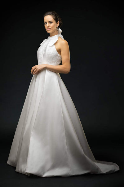 Bride wearing silk mikado halter dress with lace detailing on the front bodice and gathered bow neckline wedding dress