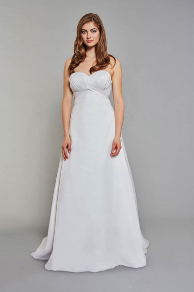 Bride wearing strapless gown with an empire waist and subtle pleated detailing on the bodice wedding dress