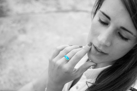 A black and white photo of a young woman. Shown in color, a blue opal ring with a gold band is worn on her finger.