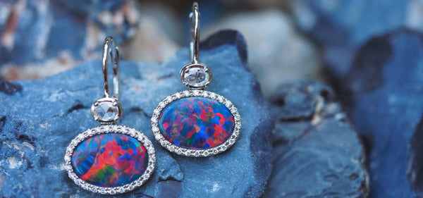 A pair of Australian black opal earrings set against potch opal stone