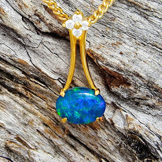 Exquisite gold plated sterling silver chandelier design slide necklace pendant claw set sideways with a blue and green oval triplet opal and four cubic zircons.