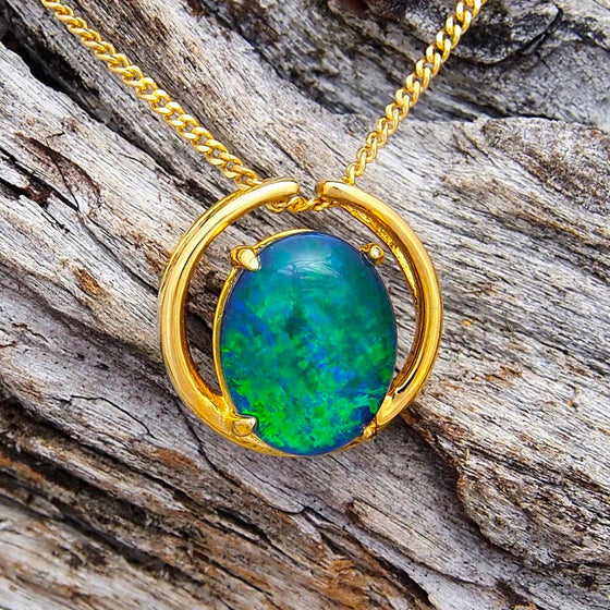 Modern gold plated sterling silver open circle design slide necklace pendant claw set with a green and blue oval triplet opal