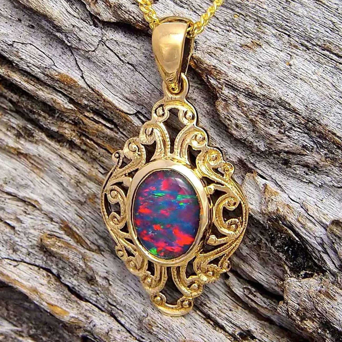 9ct yellow gold decorative design necklace pendant bezel set with a rich blue, red and green oval triplet opal
